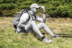 Il viaggiatore incolore dell'uomo si siede sull'erba e mette la sua mano alla visiera del cappuccio Fotografia Stock