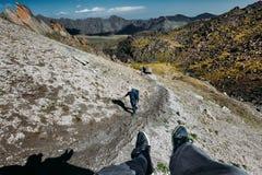 Il viaggiatore maschio si siede sulla montagna superiore e gode di Mountain View di estate Il gruppo di turisti scala in salita C immagini stock libere da diritti