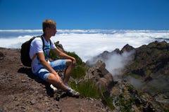 Il viaggiatore si siede ha un resto alla cima della montagna Immagini Stock Libere da Diritti