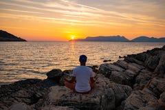 Il viaggiatore si siede sulla spiaggia della roccia e sull'yoga di pratica fotografie stock libere da diritti