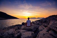 Il viaggiatore si siede sulla spiaggia della roccia e sull'yoga di pratica immagini stock libere da diritti