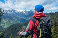 Il viaggiatore sicuro dell'uomo in occhiali da sole sta nelle montagne Fotografia Stock