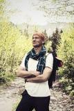 Il viaggiatore sorridente dell'uomo sta sulla strada della montagna Fotografie Stock Libere da Diritti