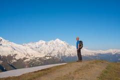 Il viaggiatore sta stando sulla strada della montagna Fotografia Stock