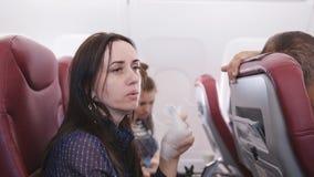 Il viaggiatore in un aereo volante ha nauseabondo La donna sull'aereo ha vomitato in un sacco di carta Passeggero di nausea in un video d archivio