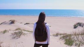 Il viaggio della ragazza sta sulla spiaggia di sabbia fra le dune e sullo sguardo alla vista posteriore di vacanza del mare stock footage
