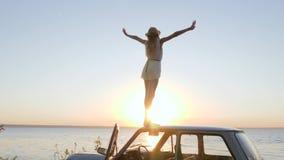 Il viaggio felice sull'automobile, giovane donna ammira il tramonto sull'argine, ragazza che sta sull'automobile del tetto con am stock footage