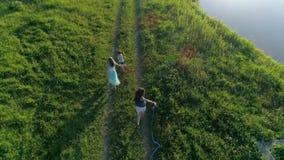 Il video aereo, bambino allegro con le ragazze dell'adolescente con i nastri colorati in mani cammina alla radura lungo il lago video d archivio