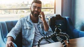 Il video blogger maschio attraente barbuto in vetri alla moda spara il video flusso continuo per gli utenti mentre si siede nella immagine stock