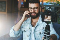Il video blogger maschio attraente barbuto in vetri alla moda spara il video flusso continuo per gli utenti mentre si siede nella immagini stock