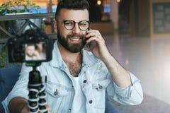 Il video blogger maschio attraente barbuto in vetri alla moda spara il video flusso continuo per gli utenti mentre si siede nella immagine stock libera da diritti