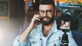 Il video blogger maschio attraente barbuto in vetri alla moda spara il video flusso continuo per gli utenti mentre si siede nella fotografia stock