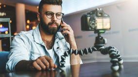 Il video blogger in vetri alla moda spara il video flusso continuo per gli utenti mentre si siede nella caffetteria e parlando su fotografia stock