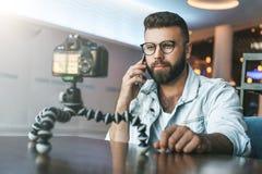 Il video blogger in vetri alla moda spara il video flusso continuo per gli utenti mentre si siede nella caffetteria e parlando su immagini stock libere da diritti