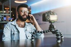 Il video blogger in vetri alla moda spara il video flusso continuo per gli utenti mentre si siede nella caffetteria e parlando su fotografie stock