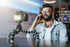 Il video blogger in vetri alla moda spara il video flusso continuo per gli utenti mentre si siede nella caffetteria e parlando su fotografia stock libera da diritti