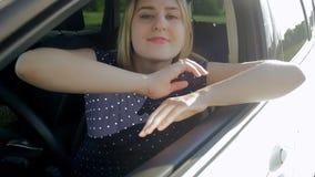 Il video di movimento lento di bella donna che conduce l'automobile apre la finestra ed osservare fuori il giorno soleggiato lumi video d archivio