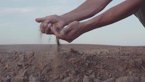 Il video di movimento lento delle mani umane del ` s tiene la siccità della polvere della terra, terra senza pioggia stock footage