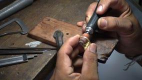 Il video di movimento lento, orafo sta lucidando un anello dell'argento o dell'oro stock footage