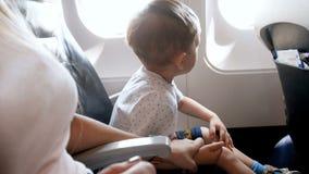 il video 4k di giovane madre che tiene suo figlio del bambino durante decolla a mano in aeroplano video d archivio