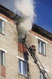 Il vigile del fuoco estingue il fuoco in un appartamento in un grattacielo Fotografia Stock Libera da Diritti