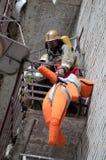 Il vigile del fuoco evacua il manichino del ` s della vittima dal balcone della combustione hous immagini stock