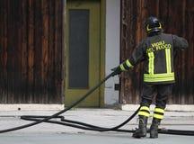Il vigile del fuoco italiano raccoglie il tubo flessibile dell'acqua dopo avere spento il fi Immagini Stock