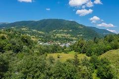 Il villaggio è situato fra gli alberi verdi della natura pittoresca vicino ad un'alta montagna Immagini Stock