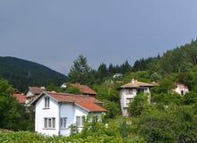 Il villaggio bulgaro tipico in una cavità fra le alte colline boscose Fotografia Stock Libera da Diritti