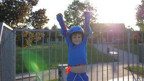 Il vincitore felice del bambino, il ragazzo nei pattini di rullo ed il casco solleva le mani su su rollerdrome all'aperto