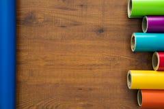 Il vinile variopinto rotola su fondo di legno Fotografia Stock
