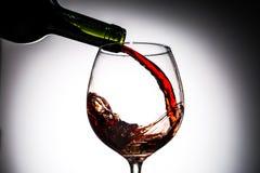 Il vino dell'uva ha versato dalla bottiglia nel vetro di vino da vetro Fotografie Stock Libere da Diritti