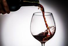 Il vino dell'uva ha versato dalla bottiglia nel vetro di vino da vetro Fotografia Stock