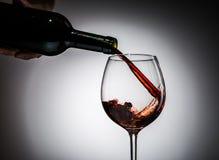 Il vino dell'uva ha versato dalla bottiglia nel vetro di vino da vetro Immagini Stock Libere da Diritti