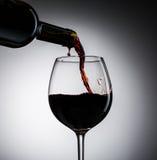 Il vino dell'uva ha versato dalla bottiglia nel vetro di vino da vetro Fotografie Stock
