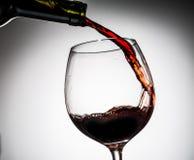 Il vino dell'uva ha versato dalla bottiglia nel vetro di vino da vetro Fotografia Stock Libera da Diritti