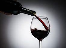 Il vino dell'uva ha versato dalla bottiglia nel vetro di vino da vetro Immagine Stock