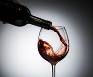 Il vino dell'uva ha versato dalla bottiglia nel vetro di vino da vetro Immagine Stock Libera da Diritti