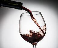 Il vino dell'uva ha versato dalla bottiglia nel vetro di vino da vetro Immagini Stock