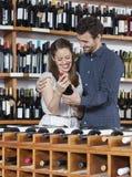 Il vino felice della tenuta delle coppie imbottiglia il negozio Fotografie Stock