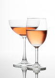 Il vino rosato d'accensione nell'insieme delle coppie di vetro di vino Immagini Stock