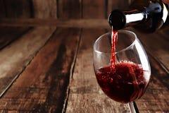 Il vino rosso è versato dalla bottiglia a vetro Fotografia Stock