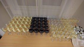 Il vino rosso e bianco ha versato dentro i vetri di vino di vetro, stanti alla scrivania con i rinfreschi in ufficio stock footage