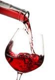 Il vino rosso ha versato dentro un vetro Immagini Stock