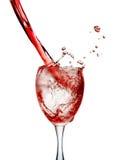 Il vino rosso ha versato dentro un vetro su fondo bianco Immagine Stock