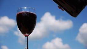 Il vino rosso ha versato in vetro dalla bottiglia video d archivio