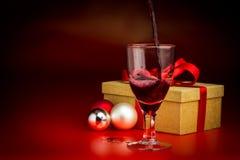 Il vino rosso ha versato in vetro davanti al presente dorato Fotografia Stock