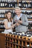 Il vino sorridente della tenuta delle coppie imbottiglia il negozio Immagine Stock