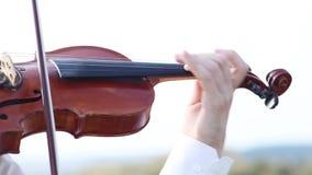 Il violinista gioca il violino su un plateau roccioso video d archivio