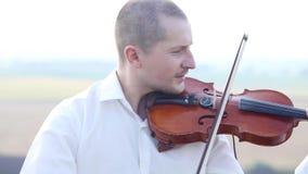 Il violinista gioca il violino su un plateau roccioso archivi video